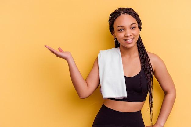 Jeune femme afro-américaine de sport tenant une serviette isolée sur fond jaune montrant un espace de copie sur une paume et tenant une autre main sur la taille.