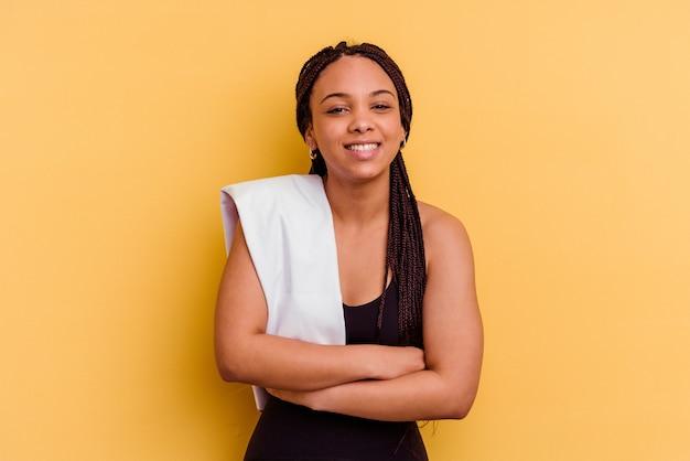 Jeune femme afro-américaine de sport tenant une serviette isolée sur fond jaune en riant et en s'amusant.