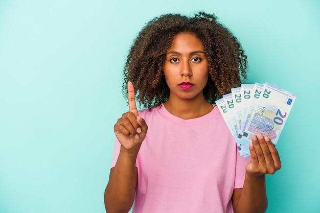 Jeune femme afro-américaine tenant des billets en euros isolés sur fond bleu montrant le numéro un avec le doigt.