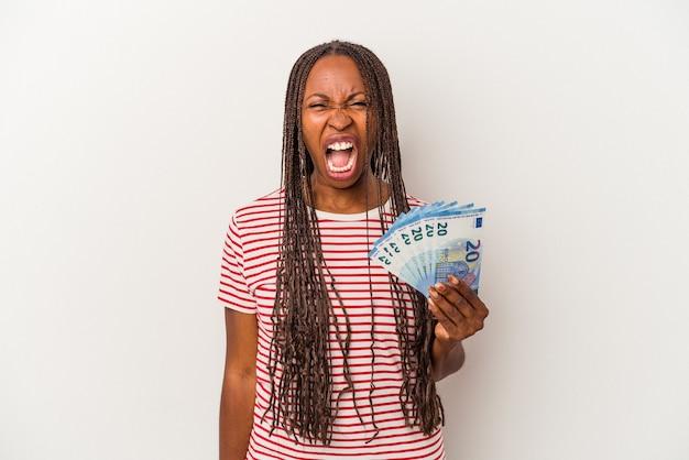 Jeune femme afro-américaine tenant des billets isolés sur fond blanc criant très en colère et agressif.