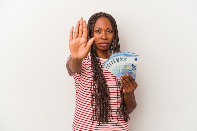 Jeune femme afro-américaine tenant des billets isolés sur fond blanc, debout avec la main tendue montrant un panneau d'arrêt, vous empêchant.