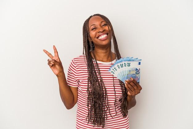 Jeune femme afro-américaine tenant des billets isolés sur fond blanc joyeux et insouciant montrant un symbole de paix avec les doigts.