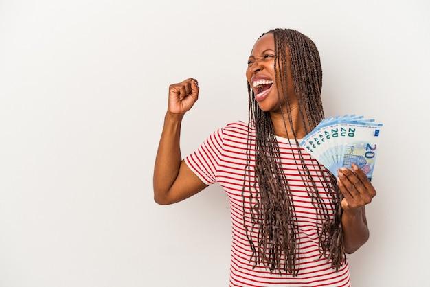 Jeune femme afro-américaine tenant des billets isolés sur fond blanc levant le poing après une victoire, concept gagnant.