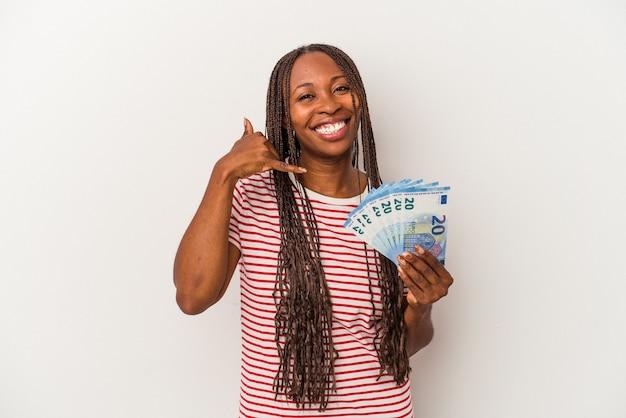 Jeune femme afro-américaine tenant des billets isolés sur fond blanc montrant un geste d'appel de téléphone portable avec les doigts.