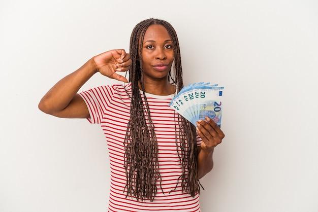 Jeune femme afro-américaine tenant des billets isolés sur fond blanc montrant un geste d'aversion, les pouces vers le bas. notion de désaccord.