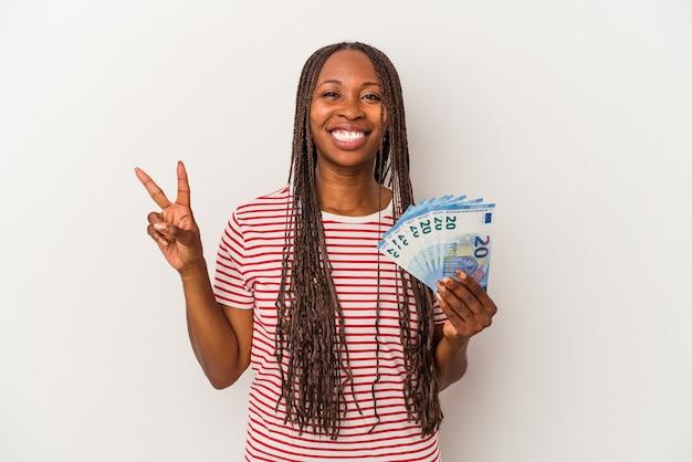 Jeune femme afro-américaine tenant des billets isolés sur fond blanc montrant le numéro deux avec les doigts.
