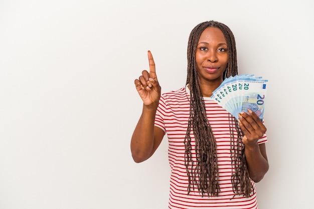 Jeune femme afro-américaine tenant des billets isolés sur fond blanc montrant le numéro un avec le doigt.
