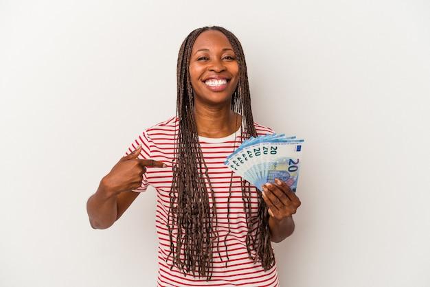 Jeune femme afro-américaine tenant des billets isolés sur fond blanc personne pointant à la main vers un espace de copie de chemise, fière et confiante