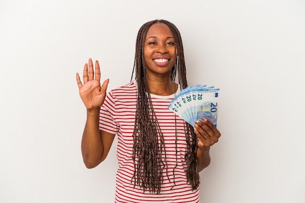 Jeune femme afro-américaine tenant des billets isolés sur fond blanc souriant joyeux montrant le numéro cinq avec les doigts.