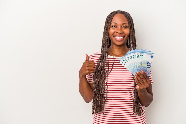Jeune femme afro-américaine tenant des billets isolés sur fond blanc souriant et levant le pouce vers le haut