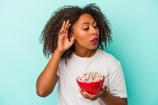 Jeune femme afro-américaine tenant un bol de céréales isolé sur fond bleu essayant d'écouter un potin.