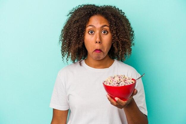 Jeune femme afro-américaine tenant un bol de céréales isolé sur fond bleu hausse les épaules et ouvre les yeux confus.