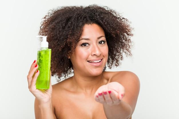 Jeune femme afro-américaine tenant une bouteille d'aloe vera pointant avec le doigt vers vous comme si vous vous invitiez à vous rapprocher.