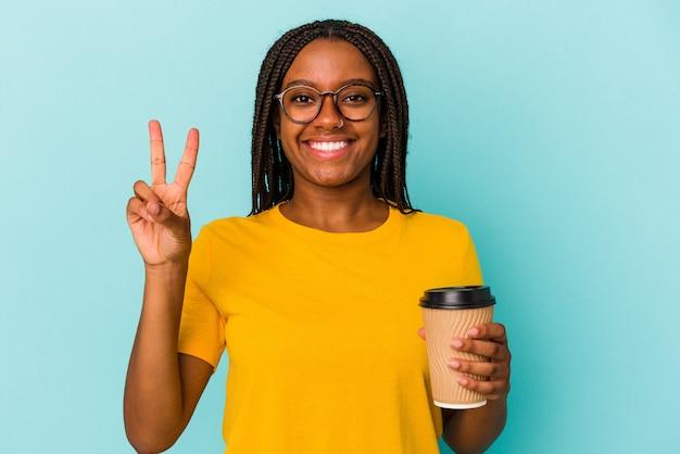 Jeune femme afro-américaine tenant un café à emporter isolé sur fond bleu montrant le numéro deux avec les doigts.