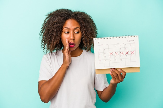 Jeune femme afro-américaine tenant un calendrier isolé sur fond bleu dit une nouvelle secrète de freinage à chaud et regarde de côté