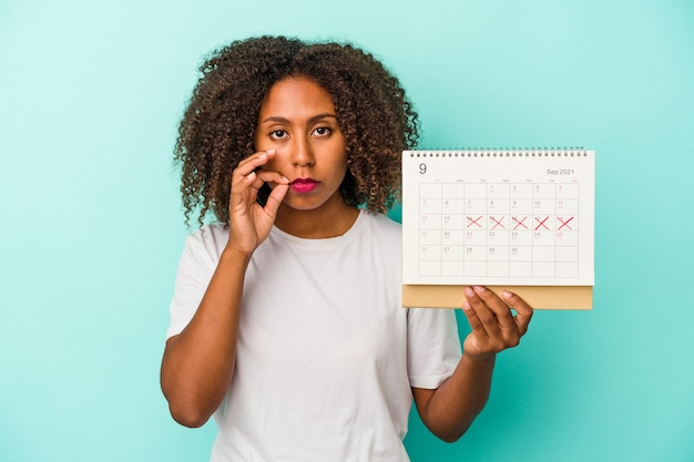 Jeune femme afro-américaine tenant un calendrier isolé sur fond bleu avec les doigts sur les lèvres gardant un secret.