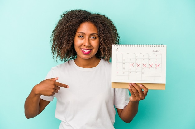Jeune femme afro-américaine tenant un calendrier isolé sur fond bleu personne pointant à la main vers un espace de copie de chemise, fière et confiante