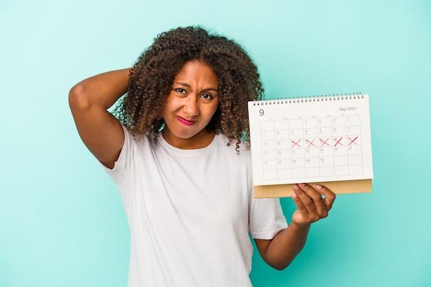 Jeune femme afro-américaine tenant un calendrier isolé sur fond bleu touchant l'arrière de la tête, pensant et faisant un choix.