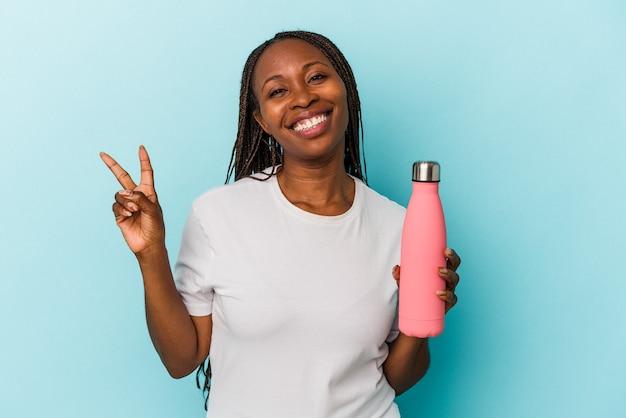 Jeune femme afro-américaine tenant une cantine isolée sur fond bleu joyeuse et insouciante montrant un symbole de paix avec les doigts.