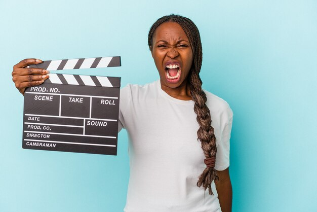 Jeune femme afro-américaine tenant un clap isolé sur fond bleu criant très en colère et agressif.