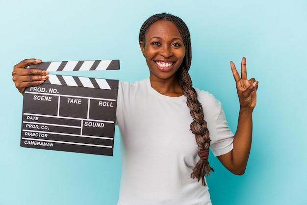 Jeune femme afro-américaine tenant un clap isolé sur fond bleu montrant le numéro deux avec les doigts.