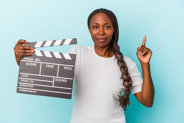 Jeune femme afro-américaine tenant un clap isolé sur fond bleu montrant le numéro un avec le doigt.