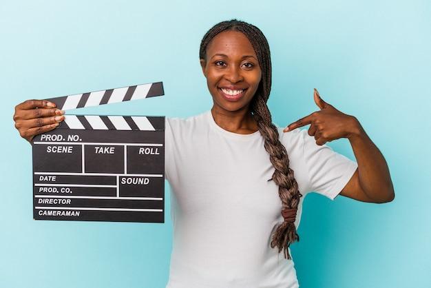 Jeune femme afro-américaine tenant un clap isolé sur fond bleu personne pointant à la main vers un espace de copie de chemise, fier et confiant