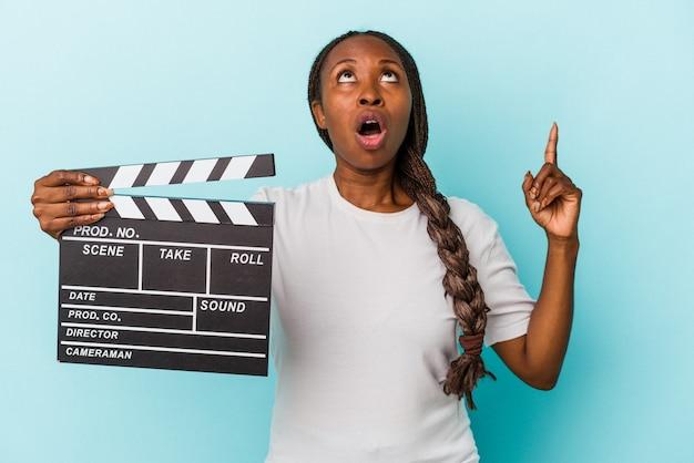 Jeune femme afro-américaine tenant un clap isolé sur fond bleu pointant vers le haut avec la bouche ouverte.