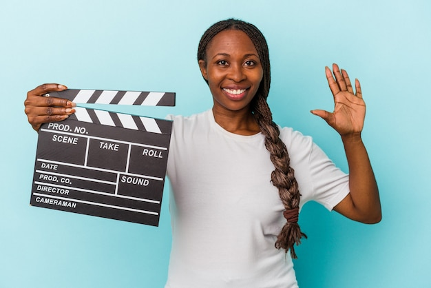 Jeune femme afro-américaine tenant un clap isolé sur fond bleu souriant joyeux montrant le numéro cinq avec les doigts.
