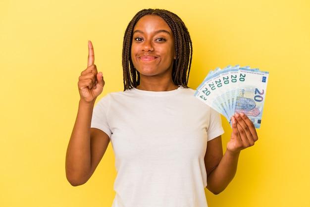 Jeune femme afro-américaine tenant des factures isolées sur fond jaune montrant le numéro un avec le doigt.