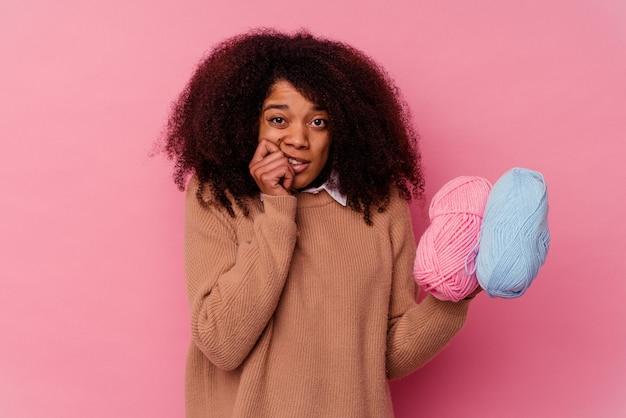Jeune femme afro-américaine tenant un fil à coudre isolé sur fond rose se rongeant les ongles, nerveuse et très anxieuse.