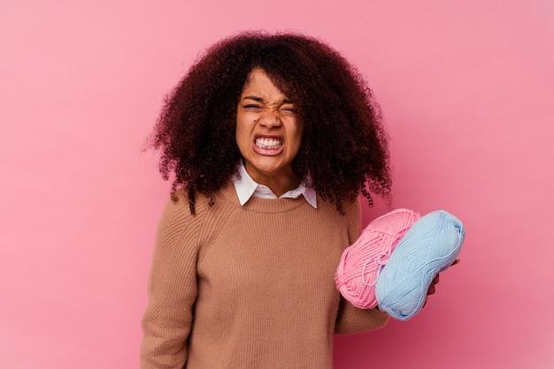 Jeune femme afro-américaine tenant un fils à coudre isolé sur fond rose criant très en colère et agressif.