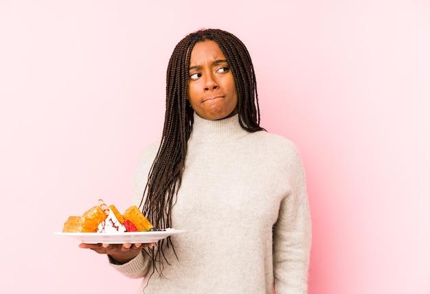 Jeune femme afro-américaine tenant une gaufre isolée confuse, se sent douteuse et incertaine.
