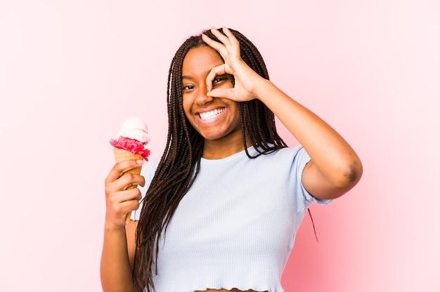 Jeune femme afro-américaine tenant une glace isolée excité en gardant le geste ok sur les yeux.