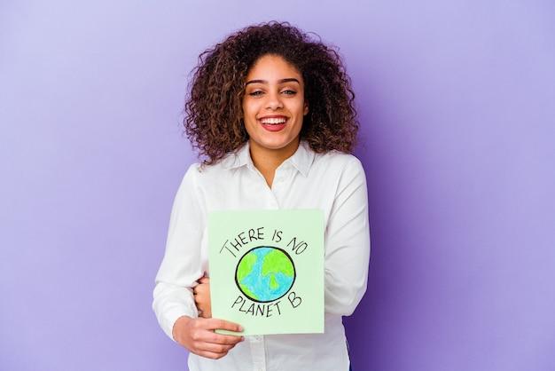 Jeune femme afro-américaine tenant un il n'y a pas de plaque-étiquette de planète b isolée en riant et en s'amusant