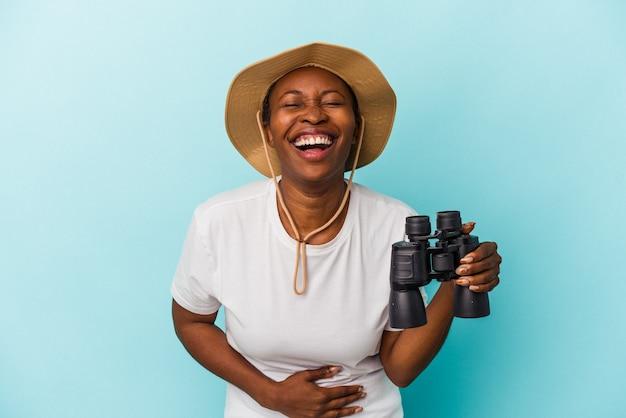 Jeune femme afro-américaine tenant des jumelles isolées sur fond bleu en riant et en s'amusant.