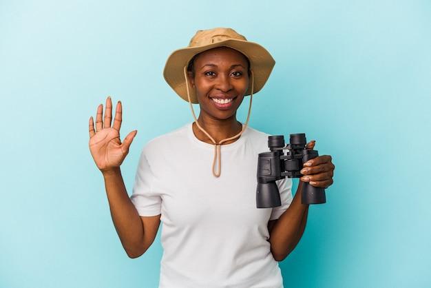 Jeune femme afro-américaine tenant des jumelles isolées sur fond bleu souriant joyeux montrant le numéro cinq avec les doigts.