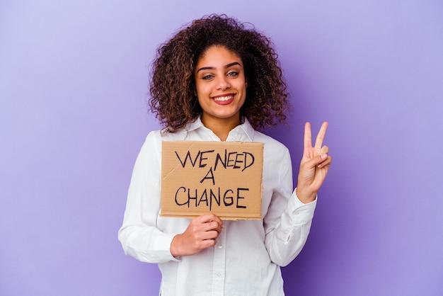 Jeune femme afro-américaine tenant un nous avons besoin d'une pancarte de changement sur violet montrant le numéro deux avec les doigts.