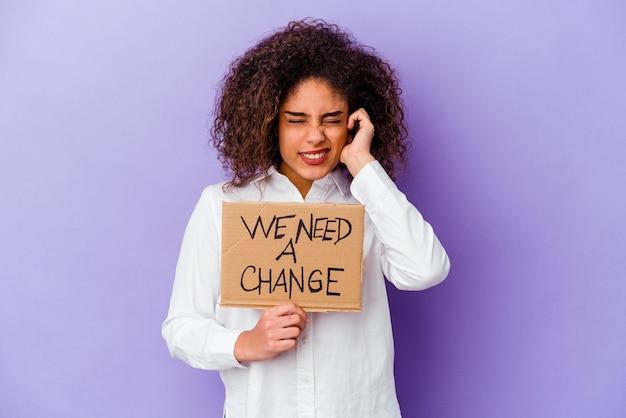 Jeune femme afro-américaine tenant un nous avons besoin d'une plaque de changement isolée