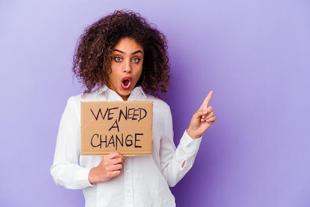 Jeune femme afro-américaine tenant un nous avons besoin d'une plaque de changement sur violet pointant vers le côté