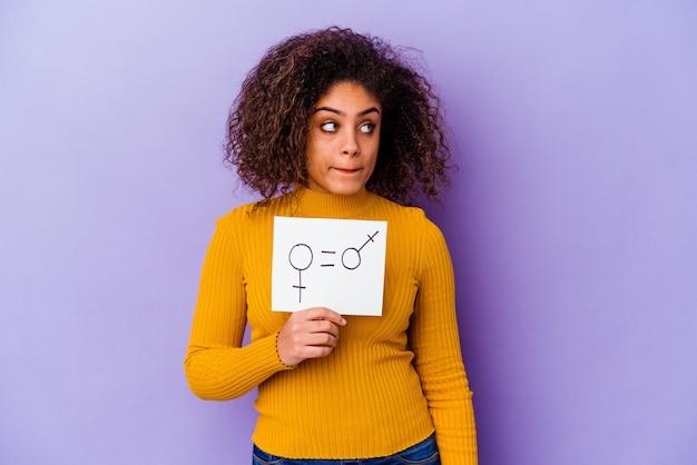 Jeune femme afro-américaine tenant une pancarte d'égalité des sexes isolée sur un mur violet confus, se sent douteux et incertain