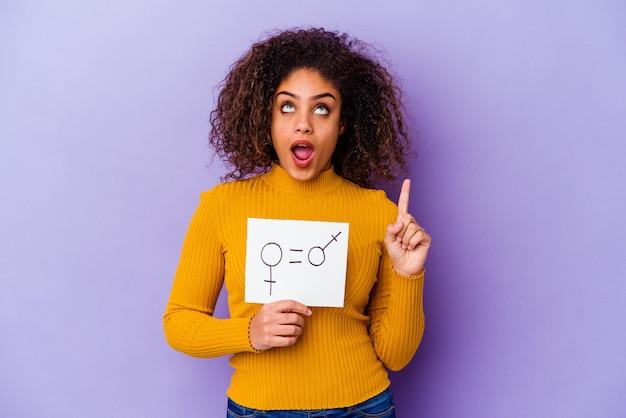 Jeune femme afro-américaine tenant une pancarte sur l'égalité des sexes sur violet pointant vers le haut avec la bouche ouverte.