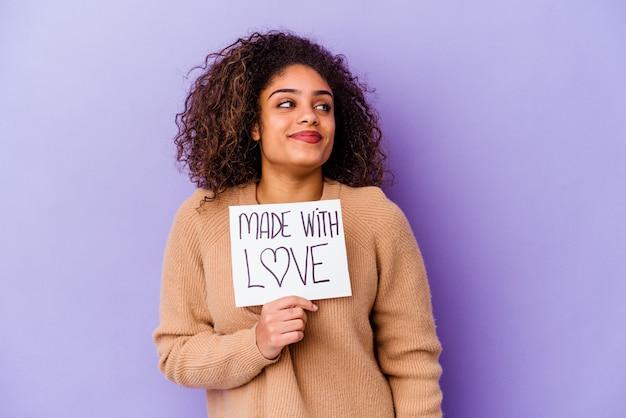 Jeune femme afro-américaine tenant une pancarte faite avec amour isolée sur fond violet rêvant d'atteindre des objectifs et des buts