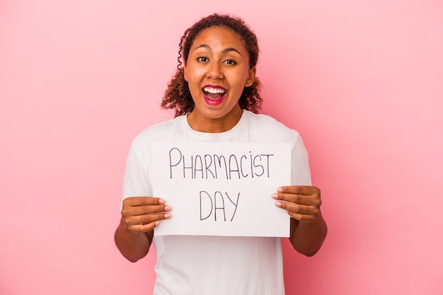 Jeune femme afro-américaine tenant une pancarte de jour de pharmacien isolée sur fond rose