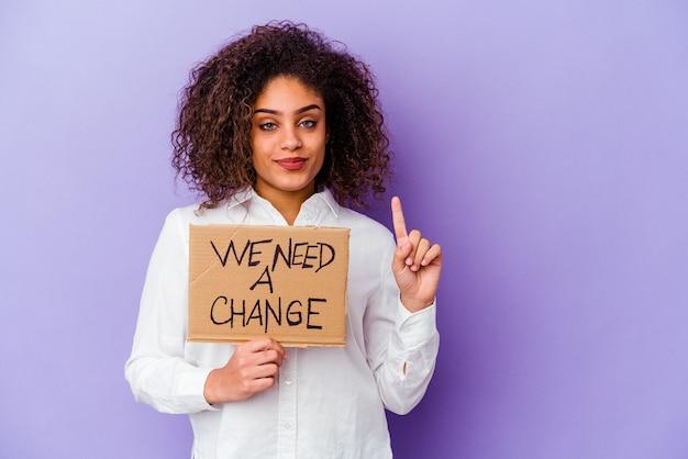 Jeune femme afro-américaine tenant une pancarte nous avons besoin d'un changement isolé sur fond violet montrant le numéro un avec le doigt.