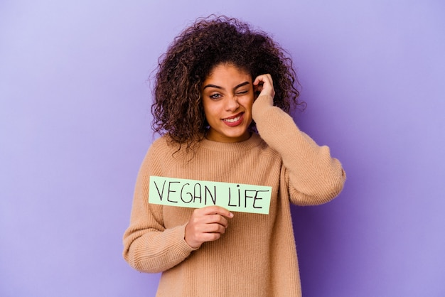 Jeune femme afro-américaine tenant une pancarte de vie végétalienne isolée couvrant les oreilles avec les mains.
