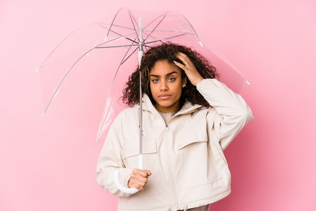 Jeune femme afro-américaine tenant un parapluie sous le choc, elle se souvient d'une réunion importante.
