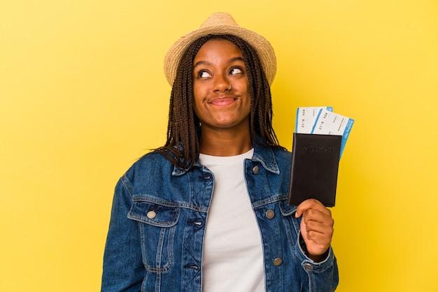 Jeune femme afro-américaine tenant un passeport isolé sur fond jaune rêvant d'atteindre des objectifs et des buts