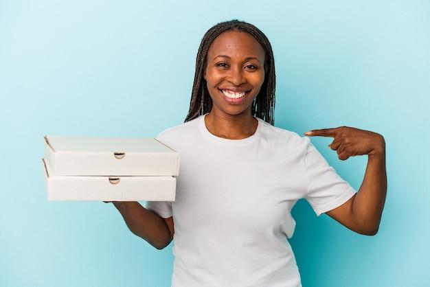 Jeune femme afro-américaine tenant des pizzas isolées sur fond bleu personne pointant à la main vers un espace de copie de chemise, fière et confiante