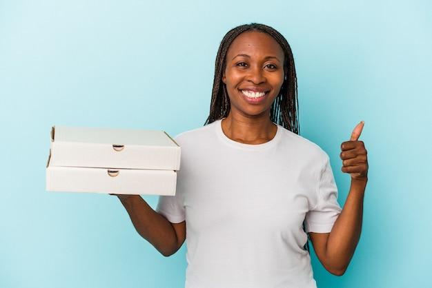 Jeune femme afro-américaine tenant des pizzas isolées sur fond bleu souriant et levant le pouce vers le haut